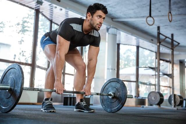Athlete wearing blue shorts and black t-shirt lifting big barbell.jpeg