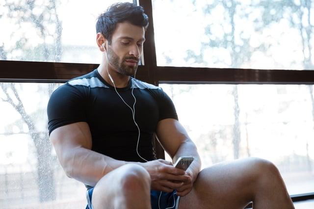 Athletic man wearing black t-shirt listening to music sitting on windowcill.jpeg
