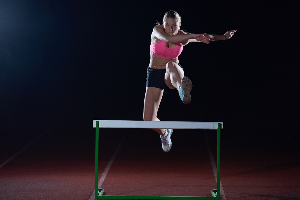Determined young woman athlete jumping over a hurdles.jpeg