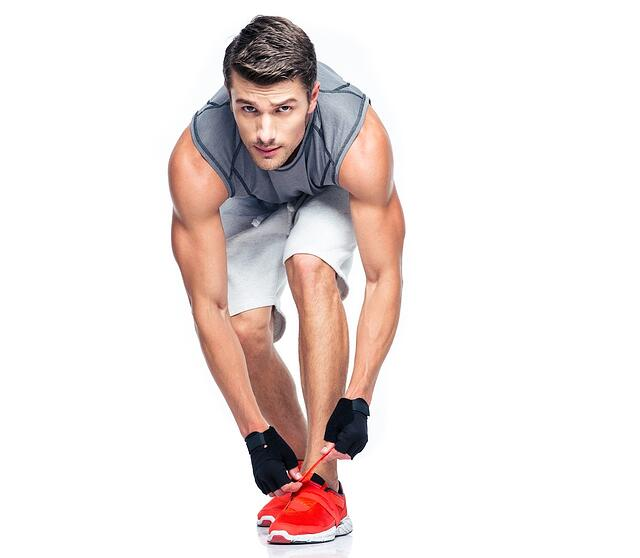 Fitness man tie shoelaces isolated on a white background. Looking at camera.jpeg