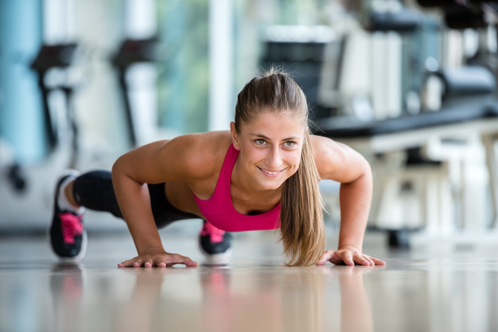 Gorgeous blonde woman warming up and doing some push ups a the gym.jpeg