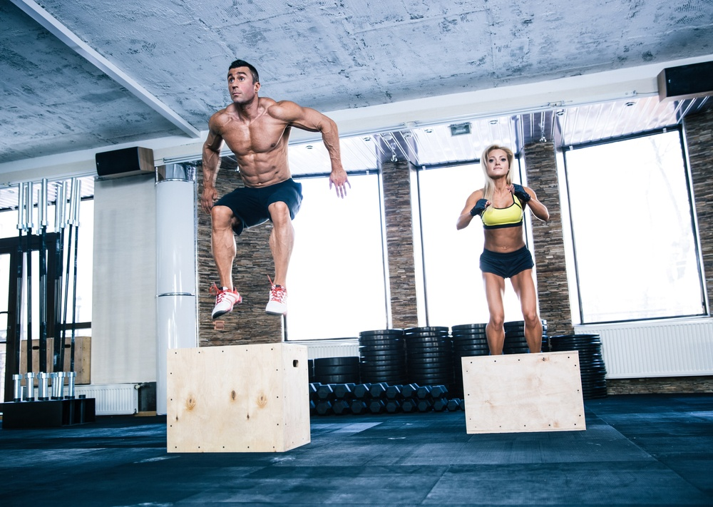 Group of man and woman jumping on fit box at gym.jpeg