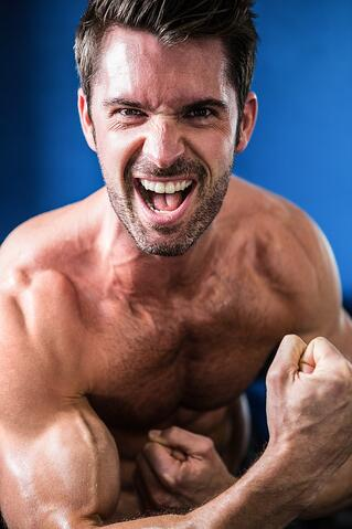 Portrait of cheerful shirtless athlete flexing muscles while standing in gym.jpeg