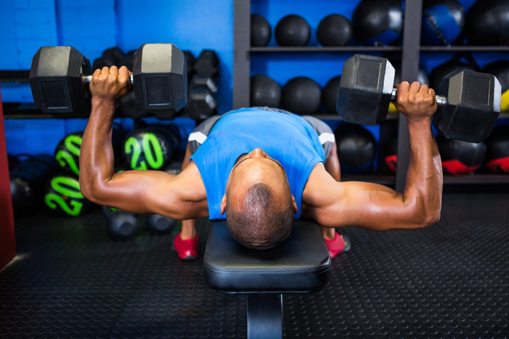 Young man exercising with dumbbells on weight bench in fitness studio.jpeg